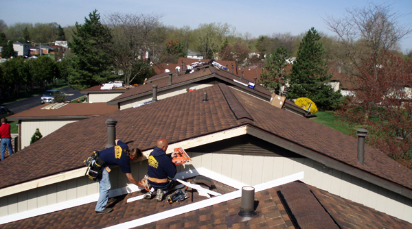 Roofers repairing and maintaining the roofs of a condominium development in Michigan
