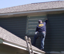 Quality Home Improvements Employee Painting Home Exterior